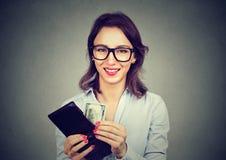Gelukkige vrouw met geld in haar portefeuille stock foto's
