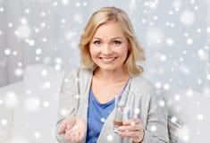 Gelukkige vrouw met geneeskunde en waterglas thuis Stock Foto's