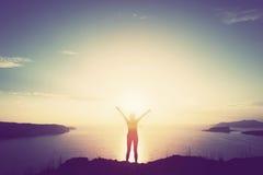 Gelukkige vrouw met handen omhoog op klip over overzees en eilanden bij zonsondergang