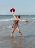 Gelukkige vrouw met hoed die op zee dansen Royalty-vrije Stock Foto's