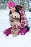 Gelukkige vrouw met hond in de winterbos Stock Afbeeldingen