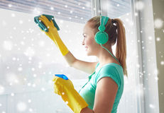 Gelukkige vrouw met hoofdtelefoons die venster schoonmaken Royalty-vrije Stock Foto