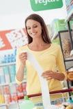 Gelukkige vrouw met kruidenierswinkelontvangstbewijs royalty-vrije stock afbeelding