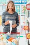 Gelukkige vrouw met kruidenierswinkelontvangstbewijs stock afbeelding