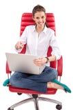Gelukkige vrouw met PC op rode stoel Royalty-vrije Stock Foto