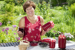 Gelukkige vrouw met potten van frambozenjam Royalty-vrije Stock Fotografie