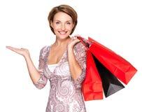 Gelukkige vrouw met presentatie gebaar en het winkelen zakken Stock Afbeelding