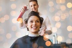 Gelukkige vrouw met stilist die kapsel maken bij salon royalty-vrije stock fotografie