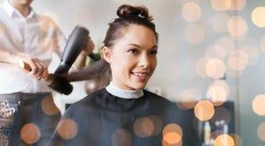 Gelukkige vrouw met stilist die kapsel maken bij salon stock afbeeldingen