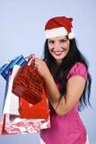 Gelukkige vrouw met van de Kerstman de hoed en van Kerstmis zakken Royalty-vrije Stock Fotografie