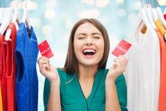 Gelukkige vrouw met verkoopmarkeringen op kleren bij garderobe Stock Foto's