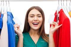 Gelukkige vrouw met verkoopmarkeringen op kleren bij garderobe Royalty-vrije Stock Afbeelding