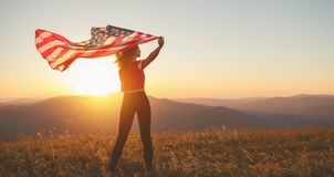 Gelukkige vrouw met vlag van Verenigde Staten die van de zonsondergang op Na genieten stock fotografie