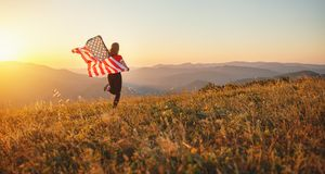 Gelukkige vrouw met vlag van Verenigde Staten die van de zonsondergang op Na genieten royalty-vrije stock afbeelding