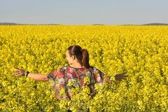 Gelukkige vrouw op bloeiend raapzaadgebied in de lente Royalty-vrije Stock Foto