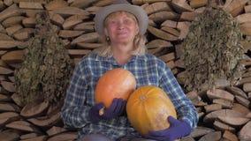 Gelukkige vrouw op een achtergrond van gestapelde brandhoutholding in haar hand rijpe pompoen stock videobeelden