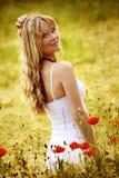 Gelukkige vrouw op een gebied met bloemen royalty-vrije stock afbeeldingen