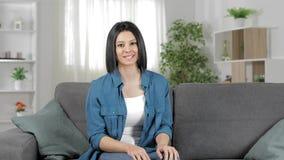 Gelukkige vrouw op een laag die bij camera thuis spreekt stock video