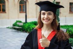 Gelukkige vrouw op haar Universiteit van de graduatiedag Onderwijs en mensen royalty-vrije stock afbeeldingen