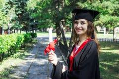 Gelukkige vrouw op haar Universiteit van de graduatiedag Onderwijs en mensen stock afbeelding