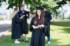 Gelukkige vrouw op haar Universiteit van de graduatiedag Onderwijs en peop stock afbeelding