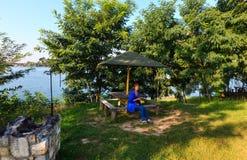 Gelukkige vrouw op het kamperen hoogte op het kalme strand van het de zomermeer Royalty-vrije Stock Foto