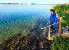 Gelukkige vrouw op het kamperen hoogte op het kalme strand van het de zomermeer Stock Foto's