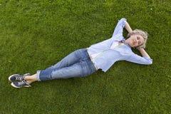 Gelukkige vrouw op middelbare leeftijd in het toevallige weekendkleding ontspannen op het gras in een park Royalty-vrije Stock Afbeeldingen
