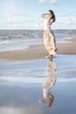 Gelukkige vrouw Portret van het mooie meisje Vrouw op het strand De wind ontwikkelt haar Royalty-vrije Stock Foto