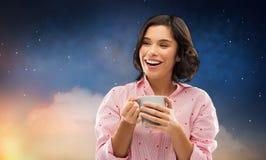 Gelukkige vrouw in pyjama met mok koffie bij nacht stock foto's