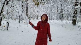 Gelukkige vrouw wat betreft takken in de winterbos, die van aard, promenade genieten stock footage