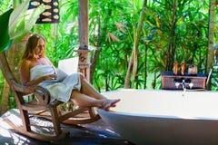 Gelukkige vrouw in werk van de buitenkant het tropische badkamers aangaande laptop computer Royalty-vrije Stock Afbeeldingen