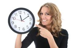 Gelukkige vrouw in zwarte met klok Stock Foto