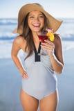 Gelukkige vrouw in zwempak die de holdingscocktail dragen van de strohoed Stock Fotografie