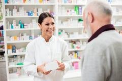 Gelukkige vrouwelijke apotheker die medicijnen geeft aan hogere mannelijke klant stock afbeeldingen