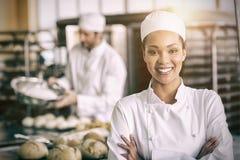 Gelukkige vrouwelijke bakker die bij camera glimlachen royalty-vrije stock fotografie
