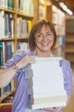 Gelukkige vrouwelijke bibliothecaris die een stapel van boeken in een bibliotheek houden stock foto