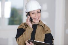 Gelukkige vrouwelijke bouwer die op telefoon spreken Stock Foto's