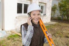 Gelukkige vrouwelijke bouwvakker op telefoon royalty-vrije stock foto