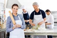 Gelukkige Vrouwelijke Chef-kok Holding Rolling Pin While Stock Afbeeldingen