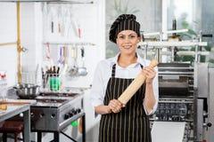 Gelukkige Vrouwelijke Chef-kok Holding Rolling Pin In Kitchen Stock Foto