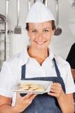 Gelukkige Vrouwelijke Chef-kok Presenting Cookies Royalty-vrije Stock Afbeelding