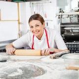 Gelukkige Vrouwelijke Chef-kok Rolling Pasta Sheet bij Teller Stock Afbeelding
