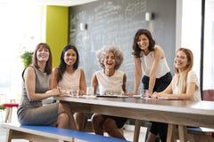 Gelukkige vrouwelijke collega's op een het werkvergadering die aan camera glimlachen stock foto's
