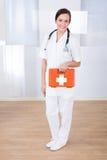 Gelukkige vrouwelijke de eerste hulpdoos van de artsenholding stock foto
