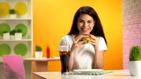 Gelukkige vrouwelijke klant die heerlijke hamburger houden en bij camera, dieet glimlachen royalty-vrije stock afbeelding