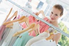 Gelukkige vrouwelijke klant die kleren in opslag selecteren Royalty-vrije Stock Afbeeldingen
