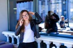 Gelukkige vrouwelijke persoon die in glazen door smartphone bij koffie spreken Stock Foto's