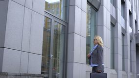 Gelukkige vrouwelijke politicus het bewonderen bezinning in de bureaubouw glas, carrière stock footage