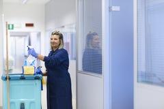 Gelukkige vrouwelijke reinigingsmachine die in bureau glimlacht Royalty-vrije Stock Afbeeldingen